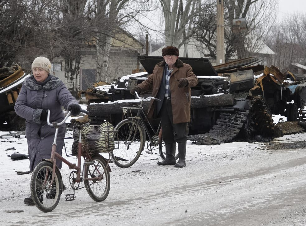 Residents pass a burnt military vehicle yesterday in Uglegorsk, not far from Debaltseve