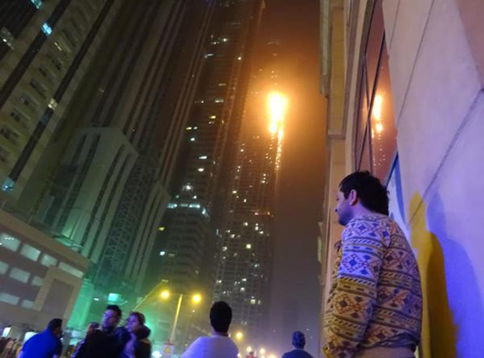 Onlookers watch as flames engulf the Torch in Dubai