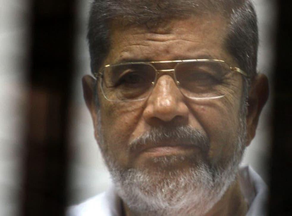 Egypt's deposed President Mohamed Morsi in the defendant's cage during his trial in Cairo last November