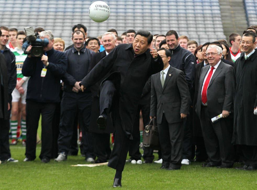 President Xi Jinping kicks a Gaelic football at Dublin's Croke Park in 2012
