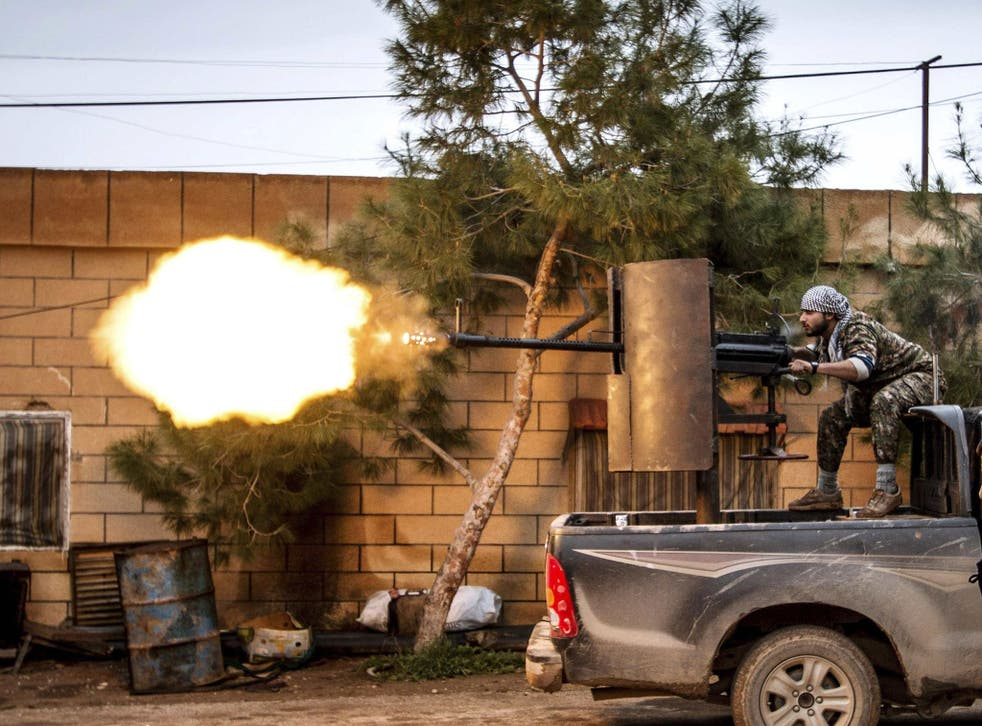 A fighter of the Kurdish People's Protection Units (YPG) fires an anti-aircraft weapon from Tel Tawil village in the direction of Isis fighters positioned in the countryside of the town of Tel Tamr