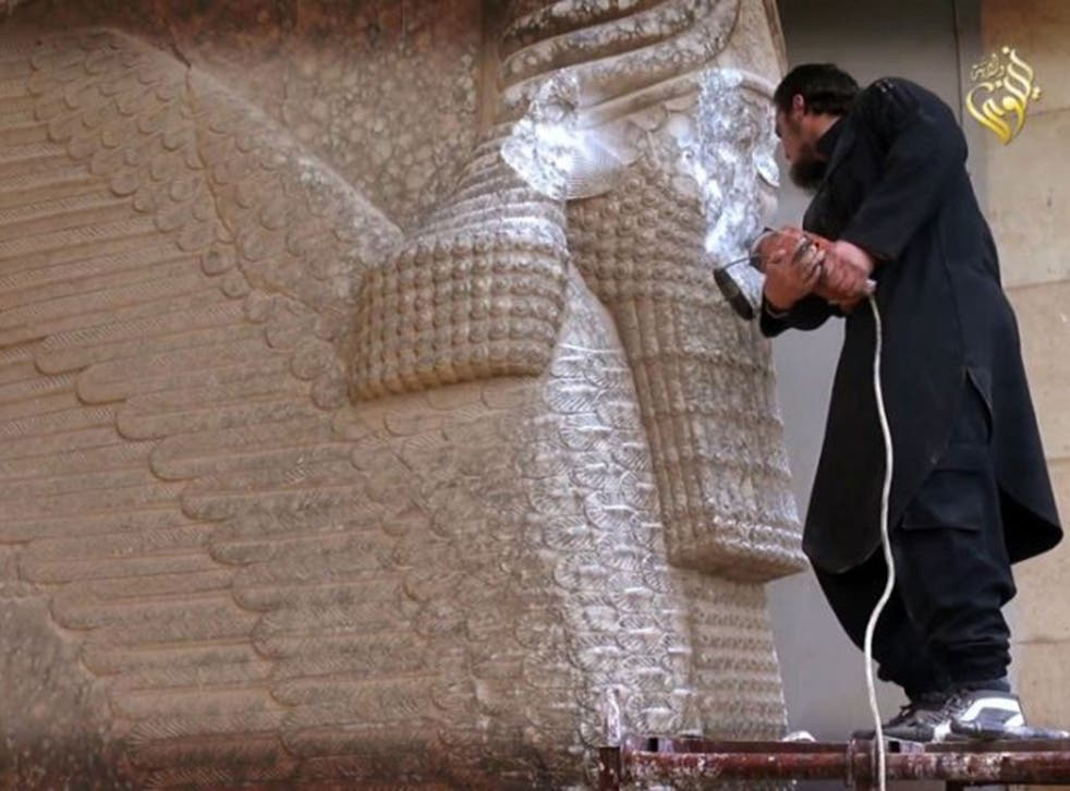 An image grab taken off a video reportedly released by Media Office of the Nineveh branch of the Islamic State (IS) Group on February 25, 2015, allegedly shows an IS militant destroying the statue of Lamassu, an Assyrian diety, with a jackhammer in the northern Iraqi Governorate of Nineveh.