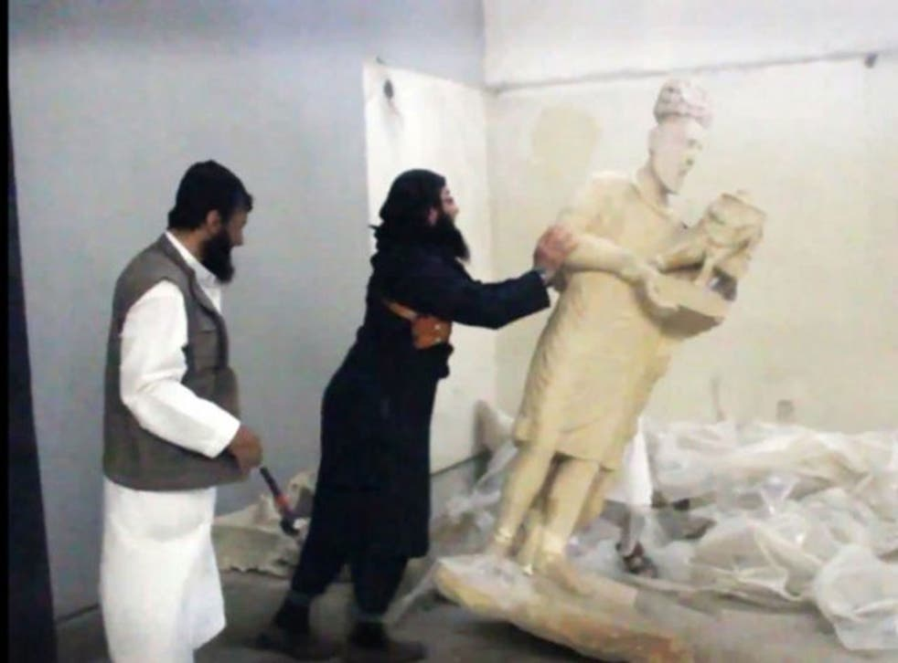 An image grab taken off a video reportedly released by Media Office of the Nineveh branch of the Islamic State (IS) Group on February 25, 2015, allegedly shows an IS militant pushing a statue inside the Mosul museum in the northern Iraqi Governorate of Ni