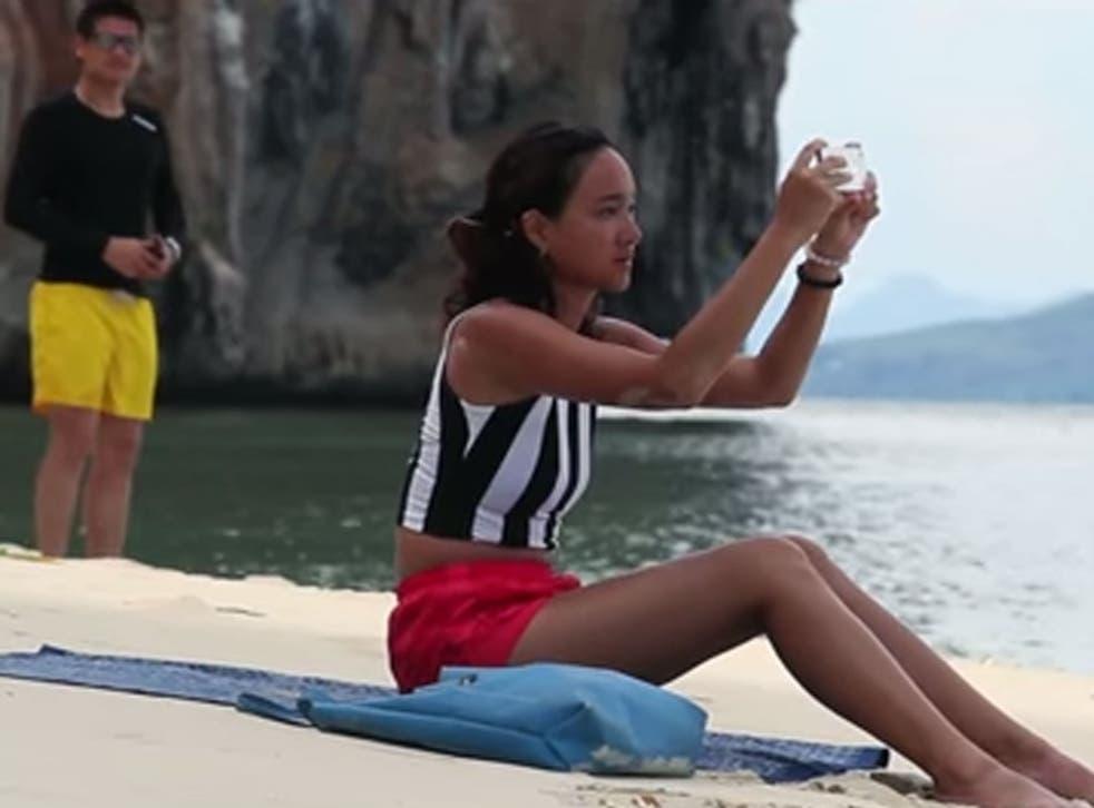 A man follows a woman onto a Thai beach without her realising
