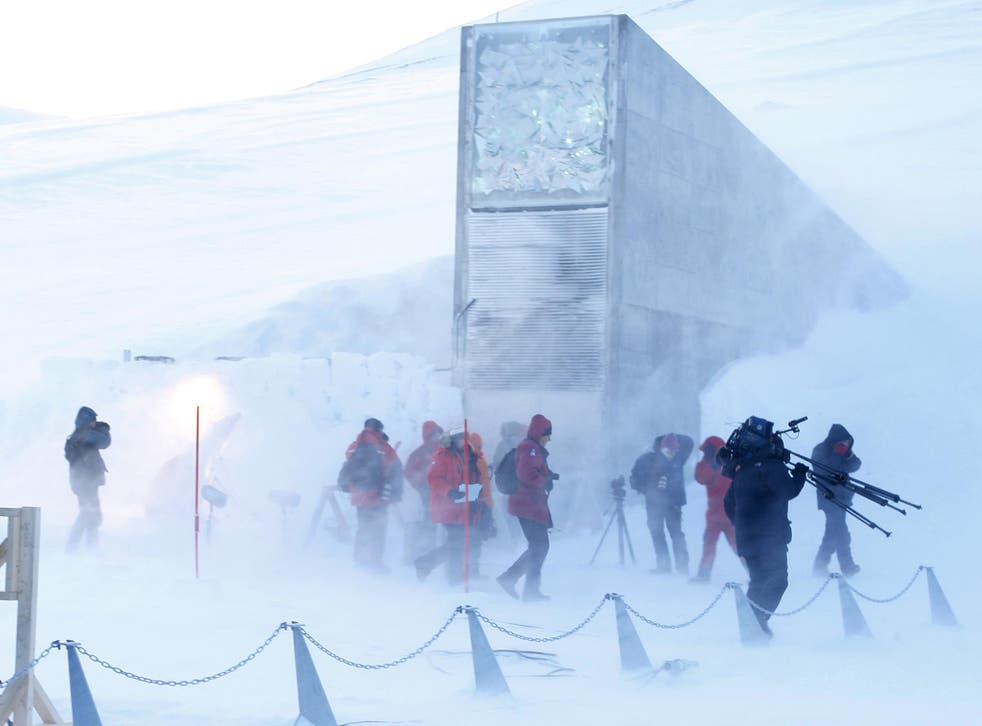 Journalists and cameramen walk near the entrance of the Svalbard Global Seed Vault