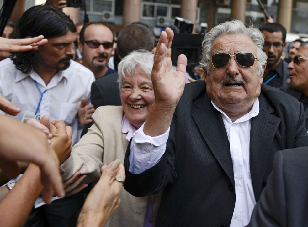 Jose Mujica with his wife being applauded and cheered on by crowds in Uruguay