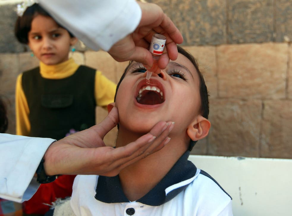 A doctor administers a polio vaccine to a child
