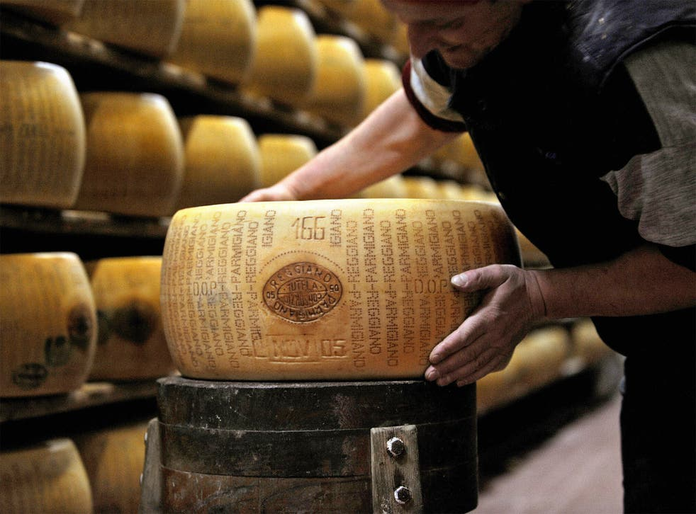 A worker checking a wheel of seasoned Parmigiano Reggiano cheese in a factory in Valestra, near Bologna