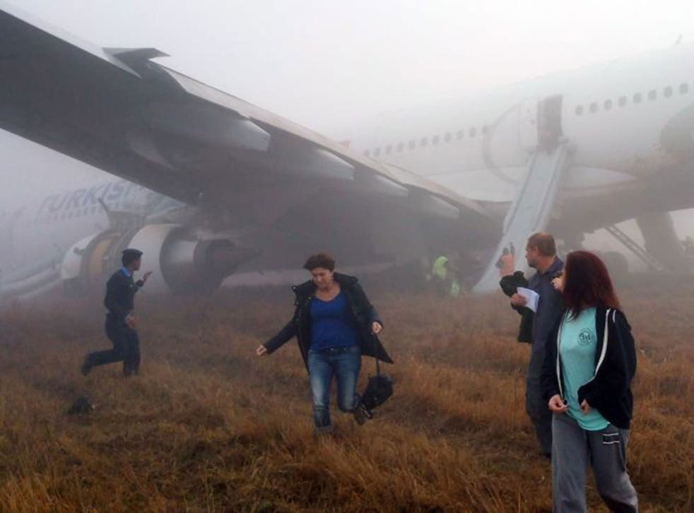Passengers walk away from a Turkish Airlines plane after it skidded off the runway while landing at Kathmandu airport