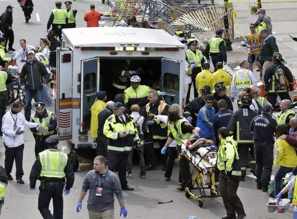 Medical workers aid injured people at the finish line of the 2013 Boston Marathon immediately following the attack