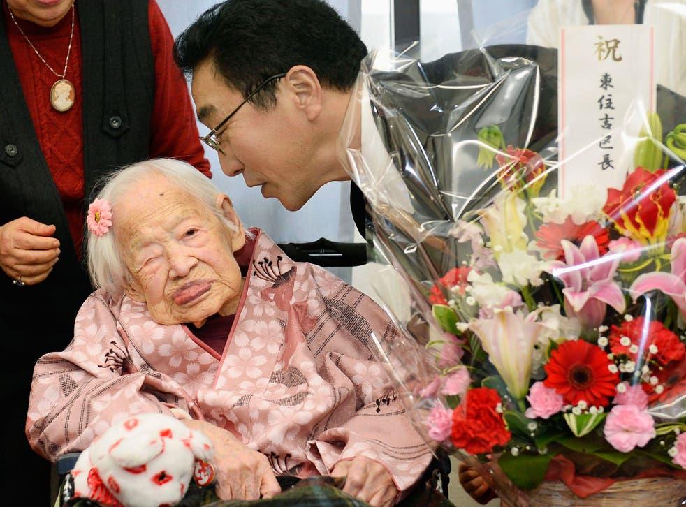 Japanese Misao Okawa, the world's oldest living person, is celebrated by Takehiro Ogura (R), mayor of Osaka's Higashi-Sumiyoshi Ward, at an elder care facility in Osaka, western Japan, the day before her 117th birthday