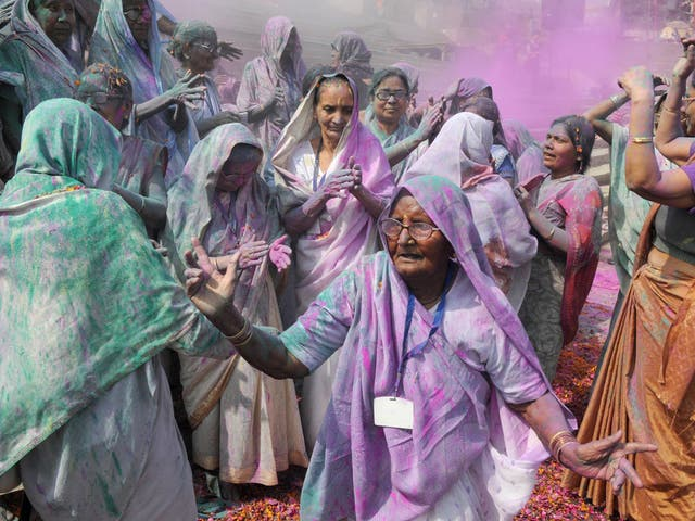 Indian villagers are covered in coloured powder during the Lathmar Holi festival at the Radha Rani temple in Barsana,India.