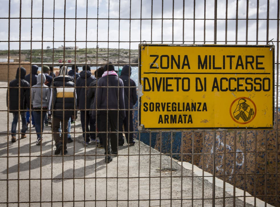 Eritrean migrant teenagers walk to the military zone of the docks of Lampedusa, Italy