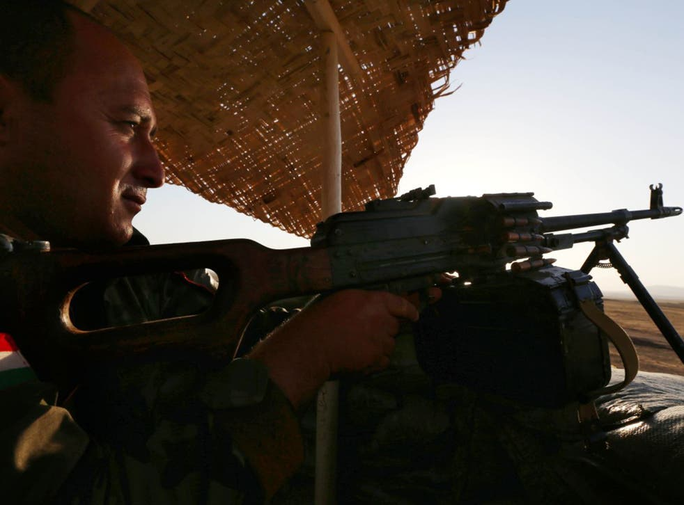 Firing line: a Peshmerga fighter mans a checkpoint to  the west of Irbil