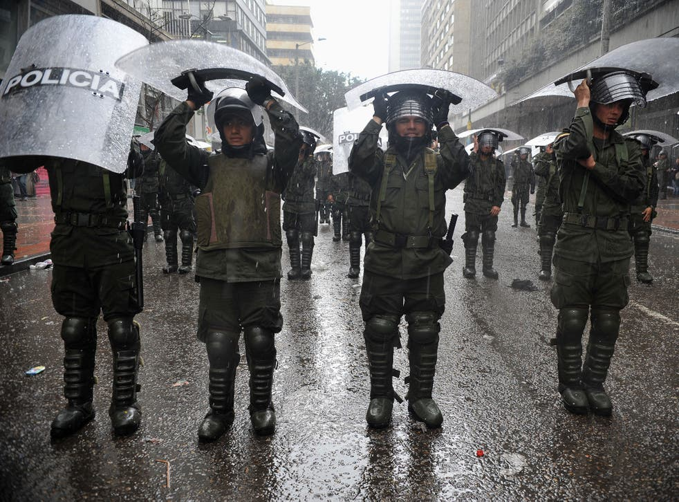 Riot police officers shelter from the rain under their shields