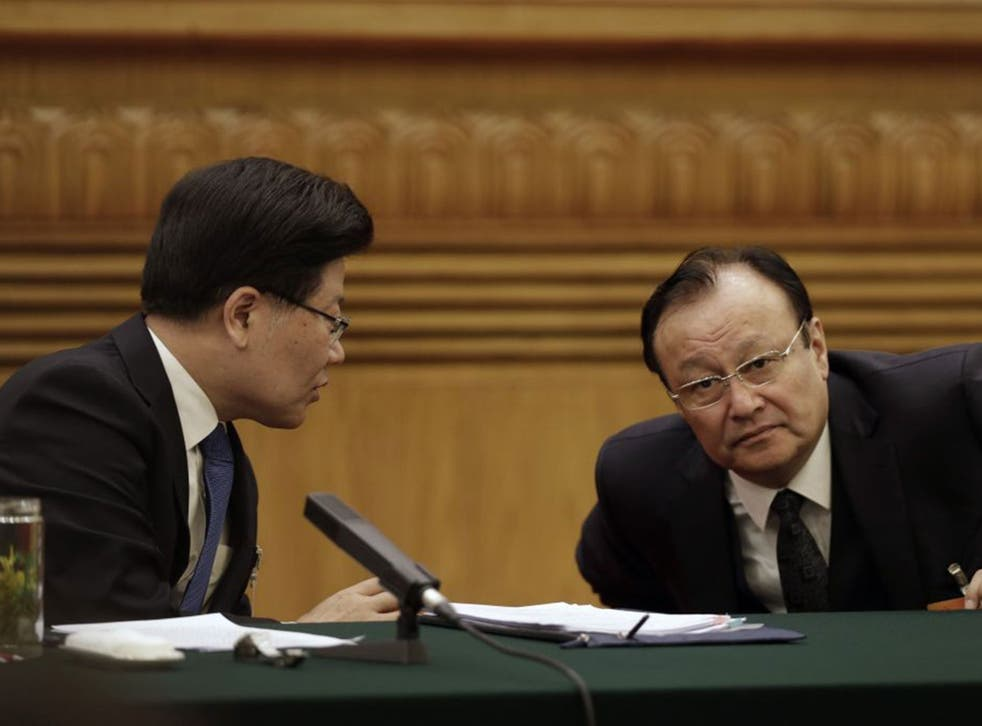 Communist Party Secretary of Xinjiang, Zhang Chunxian, left, talks with Shohrat Zakir, chairman of the Xinjiang Uyghur Autonomous Region, during thier delegation's meeting on the sideline of the National People's Congress