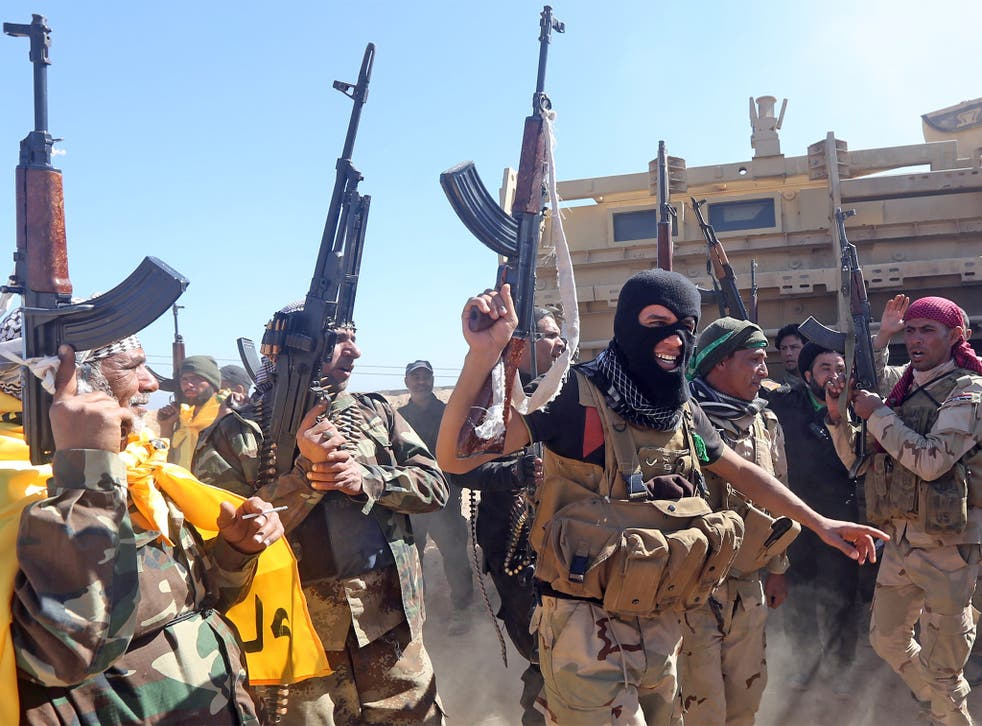 Iraqi pro-government fighters celebrate as they advance into Tikrit