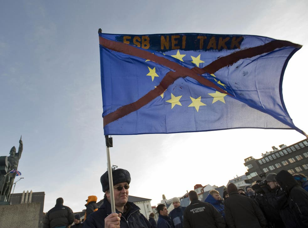 A demonstrator holds an EU flag with a red cross over it in front of the statue of Ingolfur Arnarsson, the founder of Iceland