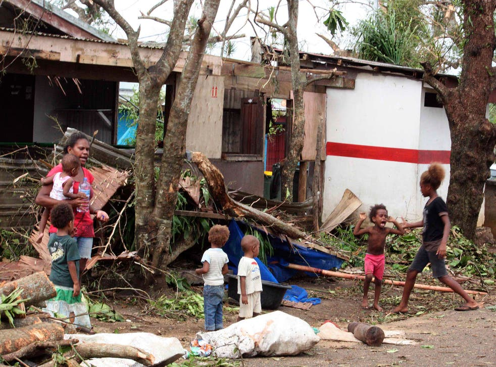 A woman carrying a baby stands with children outside homes damaged by Cyclone Pam, on a street surrounded by debris in Port Vila