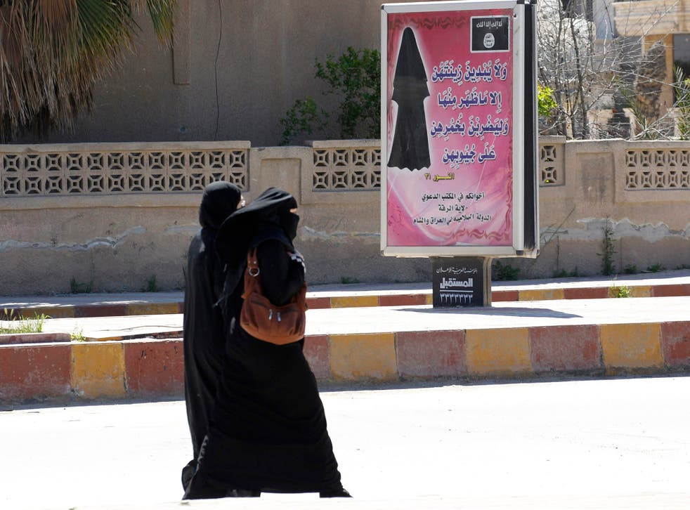 Veiled women walk past a billboard that carries a verse from Koran urging women to wear a hijab in the northern province of Raqqa (REUTERS/Stringer)