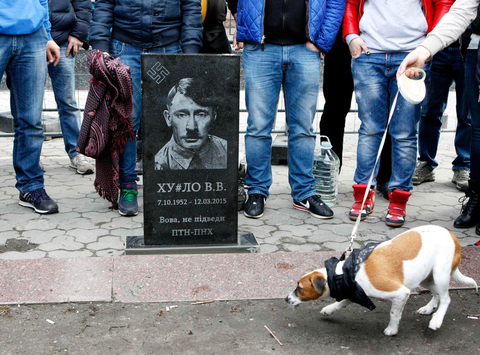A mock headstone depicting the Russian leader as Adolf Hitler during a 'Funeral of Putin' protest at the Russian embassy in Kiev