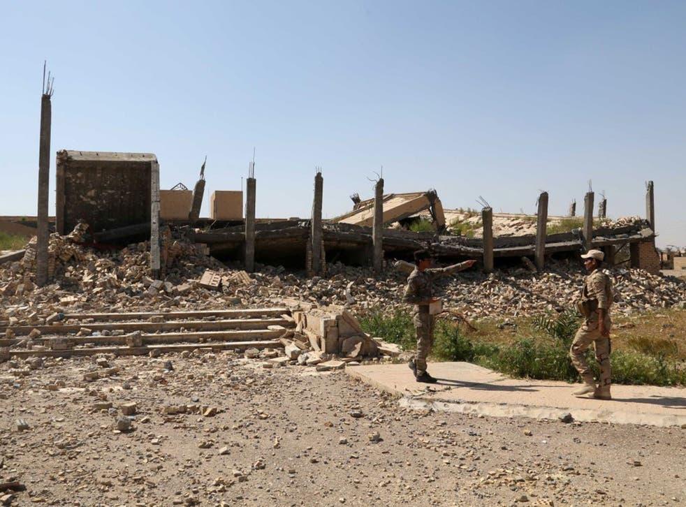 Iraqi soldiers stand next to the demolished tomb of former Iraqi president, Saddam Hussein, in Tikrit, 130km (80 miles) north of Baghdad, Iraq
