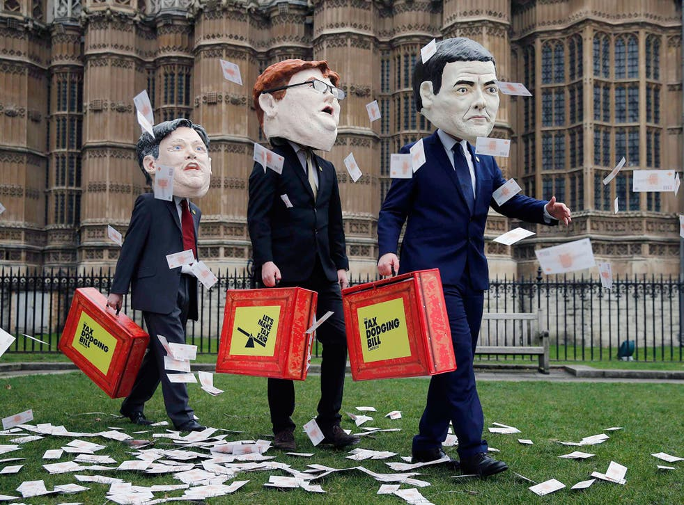 Campaigners from the Tax Dodging Bill campaign dressed up as Britain's shadow Chancellor of the Exchequer Ed Balls, Chief Secretary to the Treasury Danny Alexander, and Chancellor of the Exchequer George Osborne (L-R), participate in a publicity stunt acr