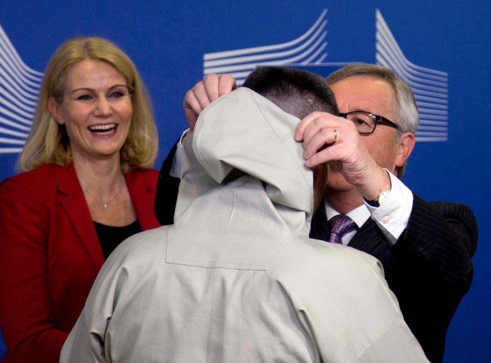 Helle Thorning-Schmidt looks on as Jean-Claude Juncker  adjusts Kim Kielsen's 'hood'