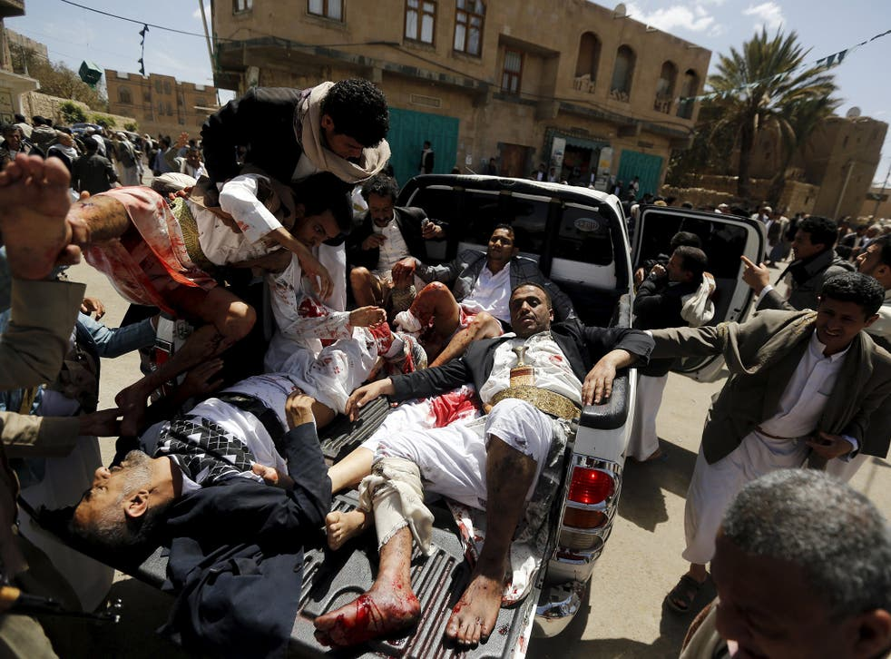 Injured worshippers are carried on to a truck to be rushed to hospital in Sanaa