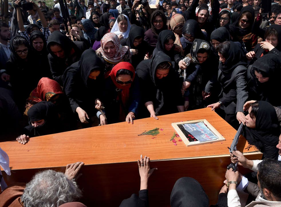 Activist women and Afghan men lower the coffin of Farkhunda at the cemetary in central Kabul