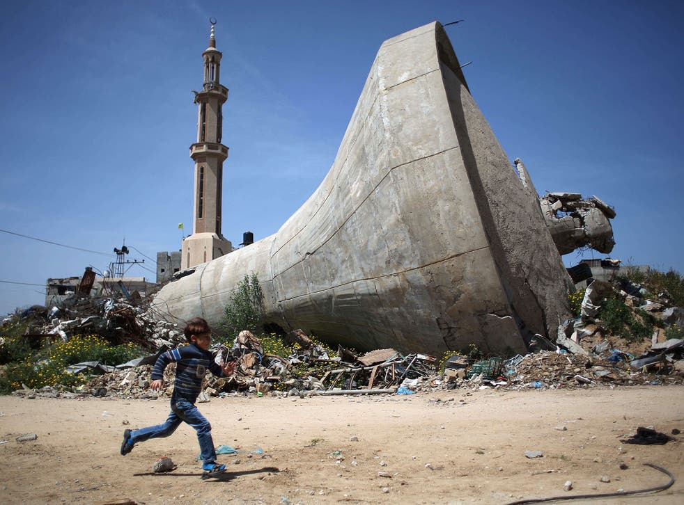 A Palestinian child runs past a water tank that was destroyed in Israeli bombing during the 50-day war between Israel and Hamas militants in the summer of 2014, in the village of Khuzaa, east of Khan Yunis, in the southern Gaza Strip