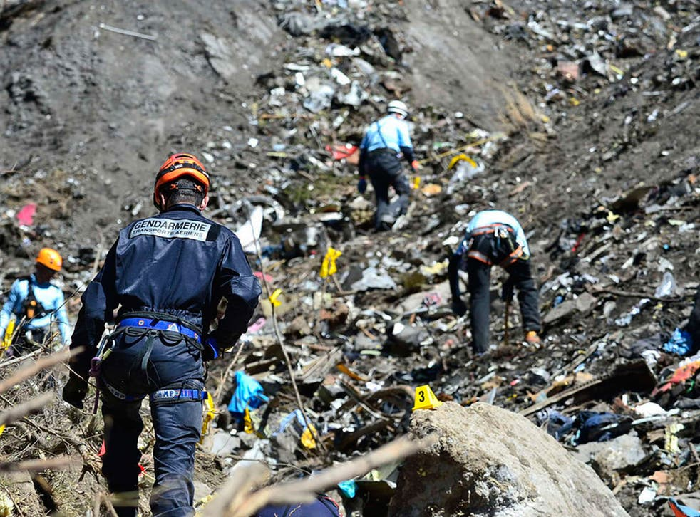 French gendarmes and investigators make their way through debris from wreckage on the mountainside at the crash site of an Airbus A320, near Seyne-les-Alpes
