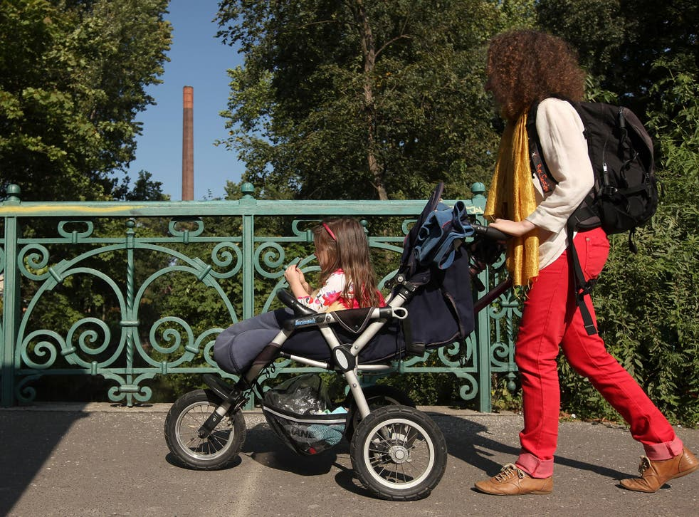 Mother pushing her daughter in a pram