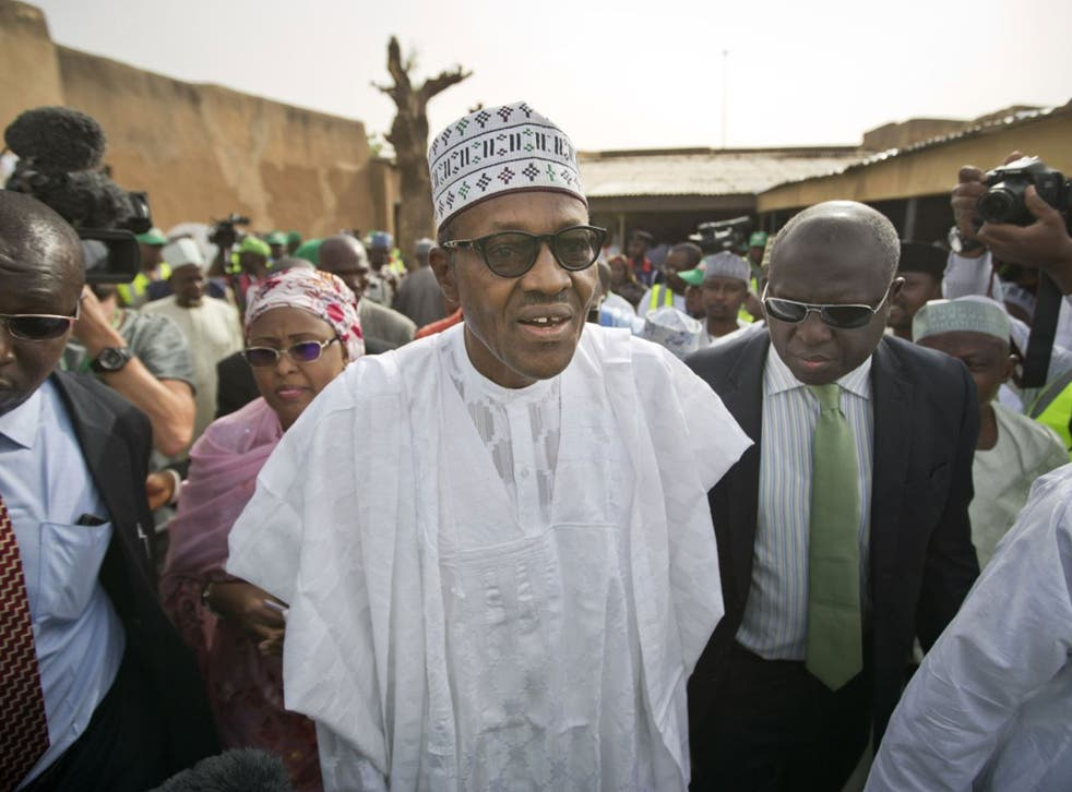 Opposition candidate Gen. Muhammadu Buhari, center, arrives to validate his voting card using a fingerprint reader, prior to casting his vote later in the day, in his home town of Daura, Nigeria Saturday, March 28, 2015. Nigerians went to the polls Saturd