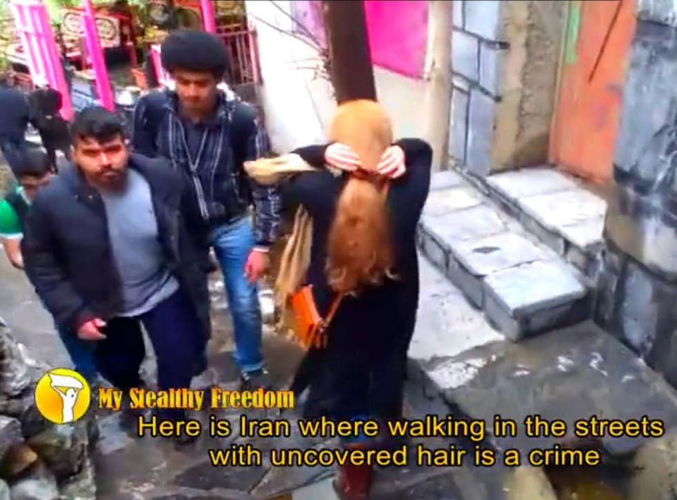 A woman walks through Tehran with her head uncovered