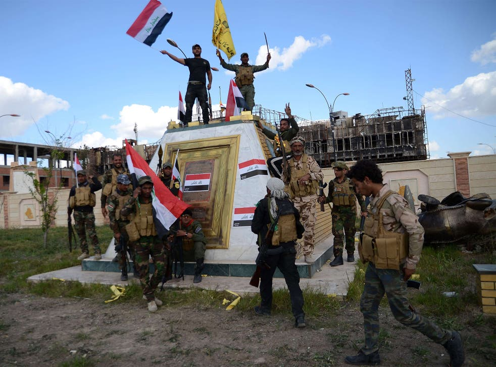 Shiite fighters celebrate in front of the the provincial council building inside the northern Iraqi city of Tikrit