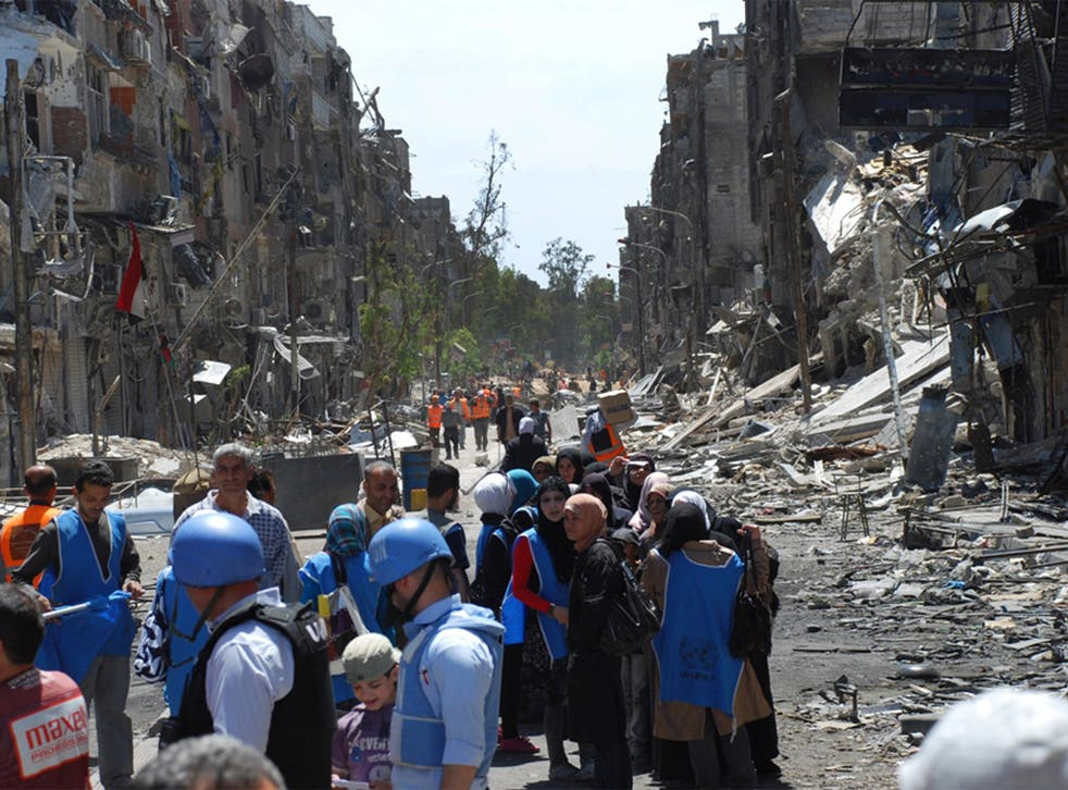 UN relief workers with local residents of the besieged Palestinian camp of Yarmouk, pictured last year