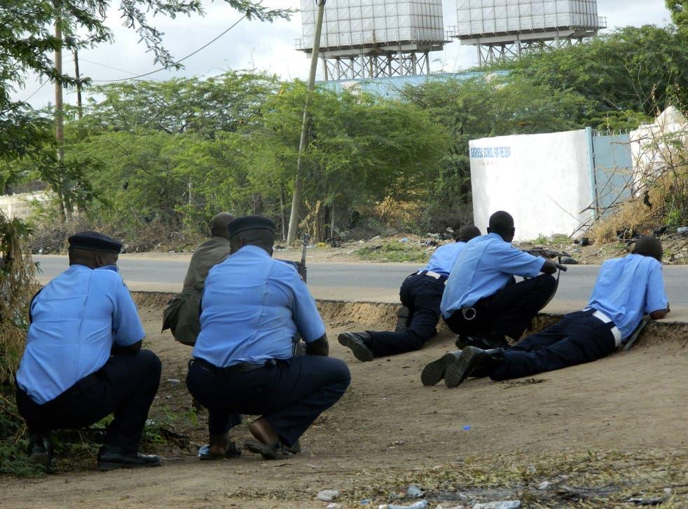 Kenyan police officers take cover outside the Garissa University College during an attack by gunmen in Garissa, Kenya