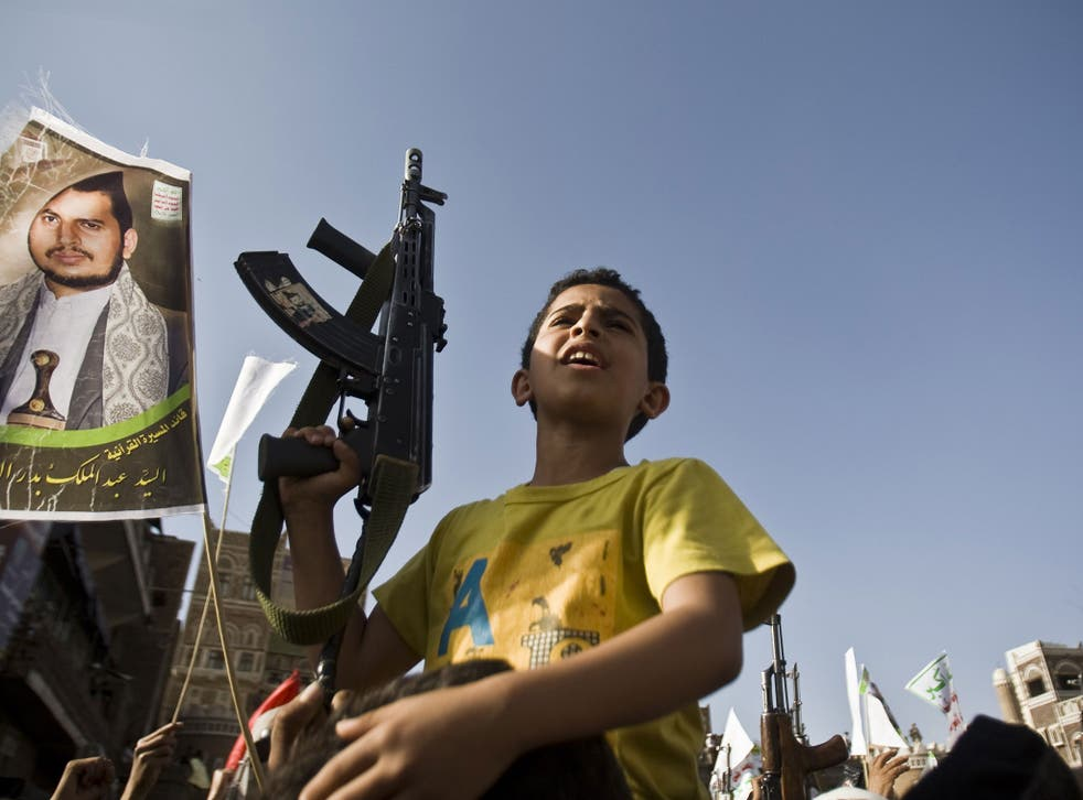 A boy holds a weapon while Shiite rebels known as Houthis protest against Saudi-led airstrikes, during a rally in Sanaa, Yemen, Wednesday, April 1, 2015