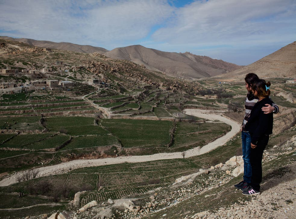 Amel and her friend Perez look out over Sinjar Mountain, February 2015