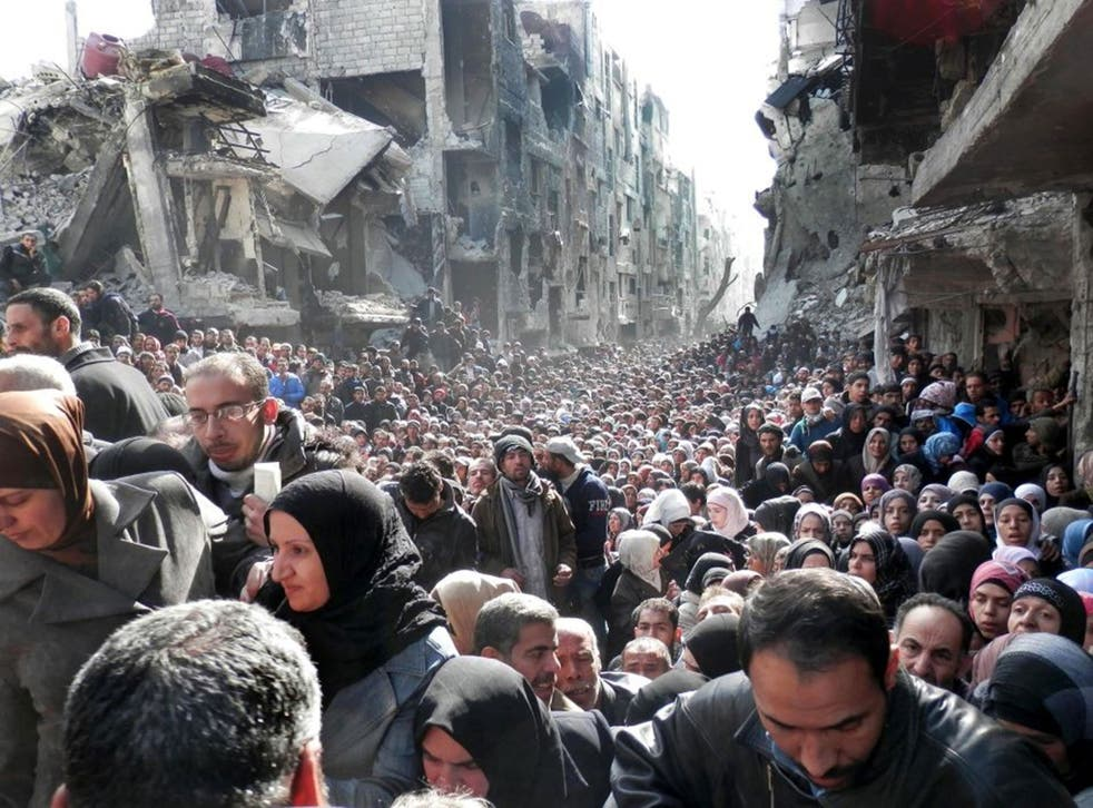 Palestinian refugees shown queuing for food supplies in the Yarmouk refugee camp last year