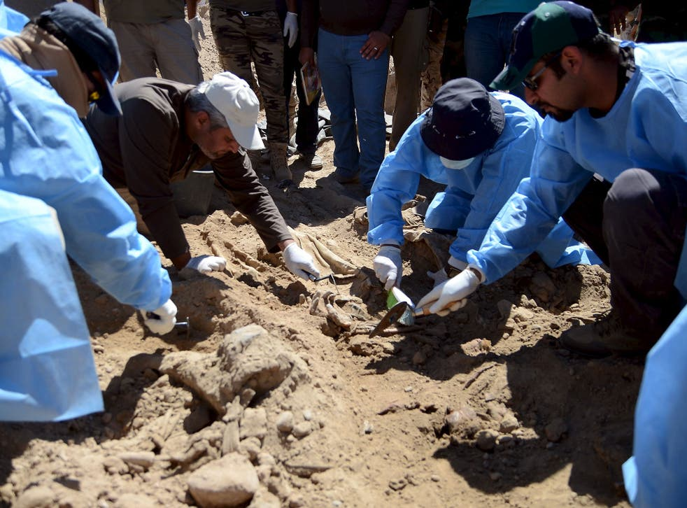 Members from the Iraqi forensic team search to extract the remains of the bodies