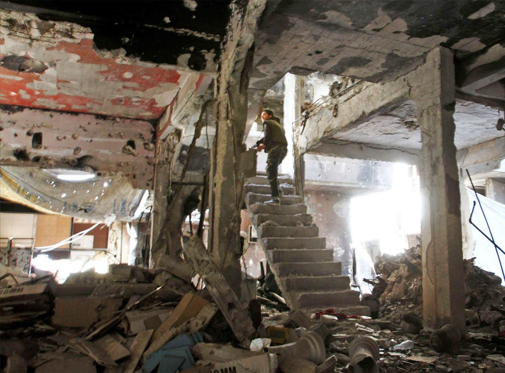 A man stands on a staircase inside a demolished building inside the Yarmuk Palestinian refugee camp