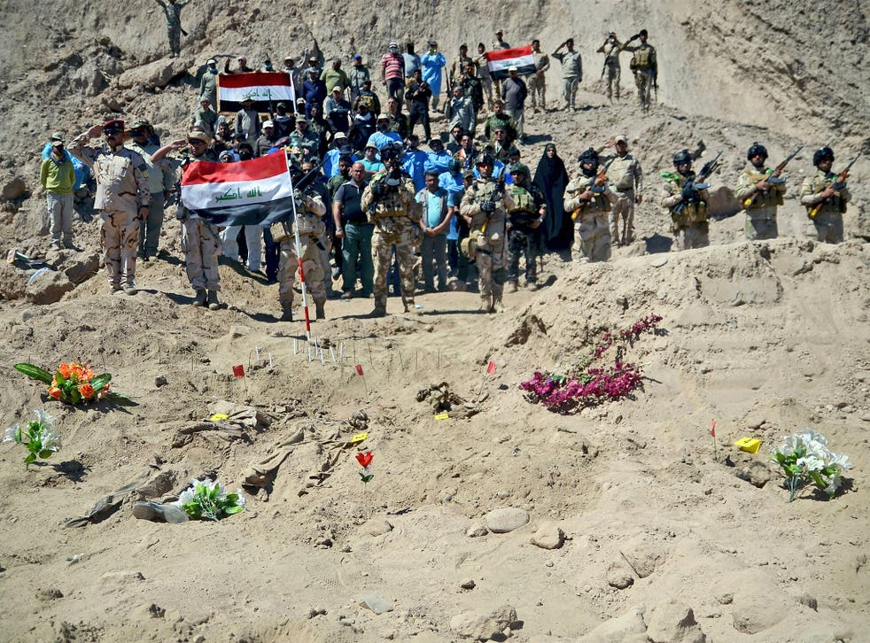 Iraqi soldiers salute as they stand next to a mass grave containing the bodies of hundreds of Shia soldiers from Camp Speicher who were killed by Isis militants in Tikrit