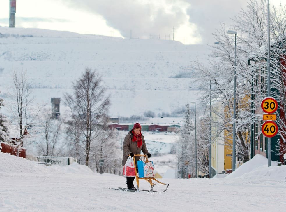 A woman rides her kick sled on a snow covered road as the iron mine of Swedish state-owned mining company LKAB (Luossavaara-Kiirunavaara Aktiebolag) at Sweden's northernmost town of Kiruna, situated in the province of Lapland is pictured on November 5, 20