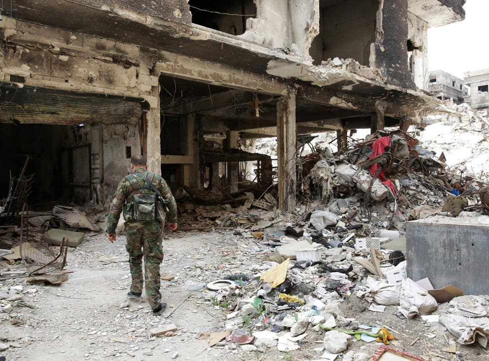 A Palestinian fighter walks through the rubble of the al-Yarmouk Palestinian refugee camp, south of Damascus, Syria