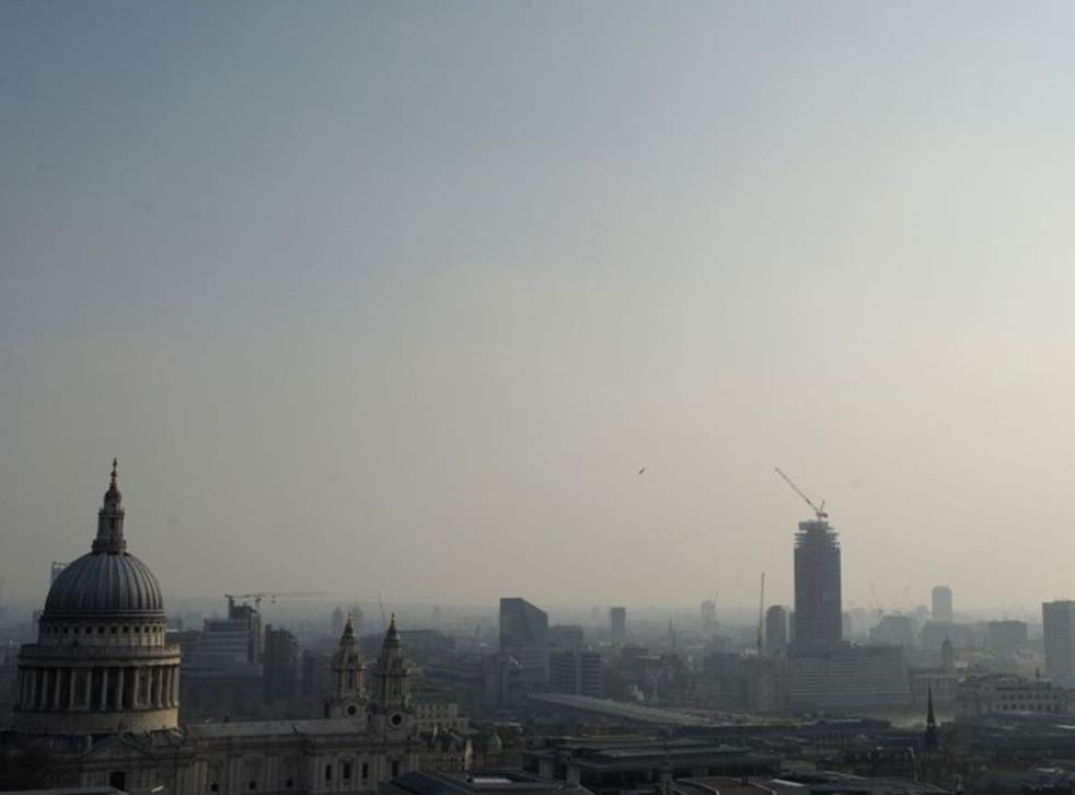 Air pollution obscures the view of the London eye with St Pauls in the foreground in central London