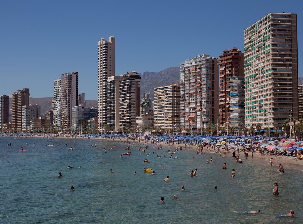 People enjoy the weather on Levante Beach in Benidorm, Spain