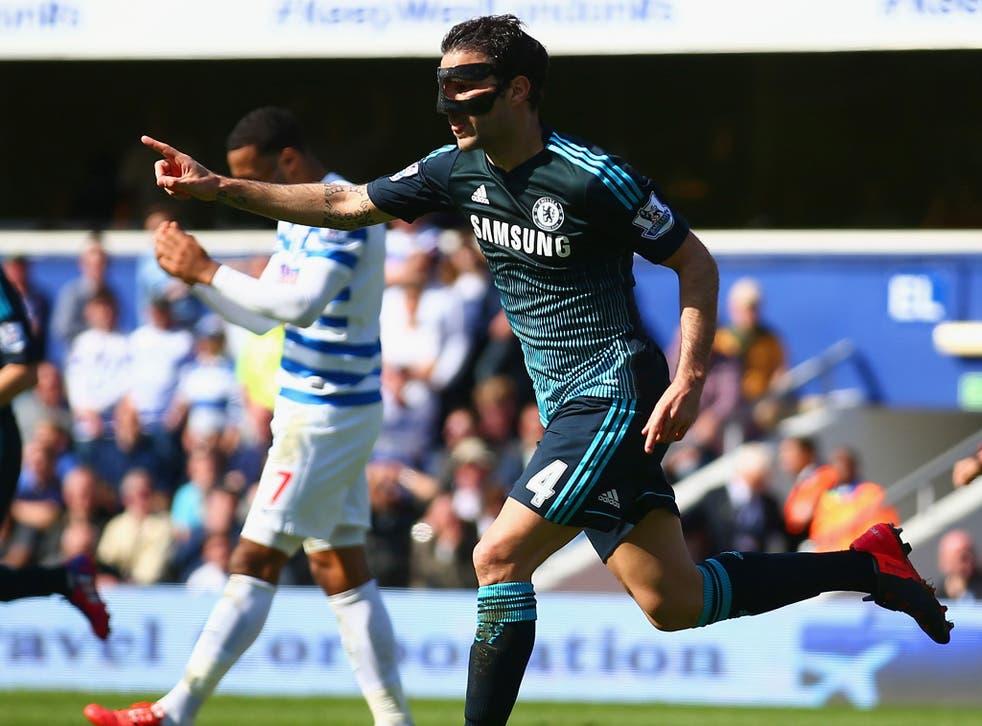 A masked Cesc Fabregas celebrates his crucial winning goal
