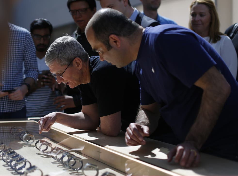 Apple CEO Tim Cook points at an Apple Watch at an Apple Store on April 10, 2015 in Palo Alto, California. The pre-orders of the highly-anticipated wearable from the tech giant begin today as the watches arrive at stores for customers to preview.